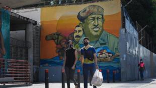 Peatones con máscaras faciales protectoras, pasan delante de un mural que representa al difunto presidente de Venezuela Hugo Chávez, el 28 de julio de 2020 en el centro de Caracas