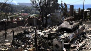 Une maison et une voiture détruites par les flammes à Tathra, en Australie, le 19 mars 2018.