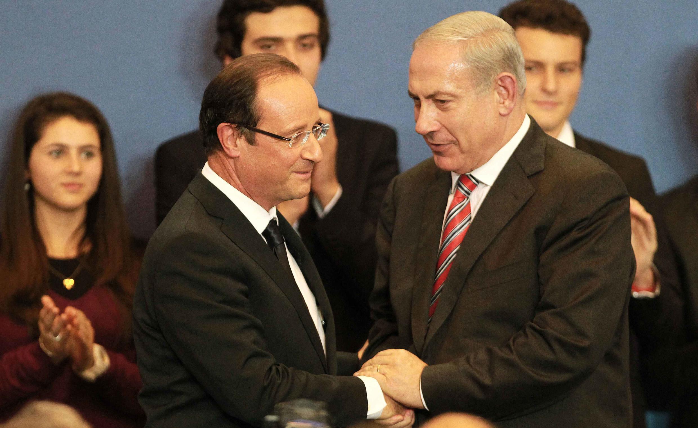 O presidente da França, François Hollande, e o primeiro-ministro israelense, Benjamin Netanyahu,  apertam as mãos durante uma cerimônia em Toulouse.