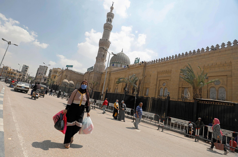 Mulher utilizando máscara de proteção contra a Covid-19 caminha diante da mesquita Sayyida Zainab, fechada pelas autoridades egípcias durante o Ramadã para evitar a propagação do coronavírus.