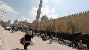Une femme portant un masque de protection marche devant la mosquée fermée Sayyida Zainab près des marchés vendant des lanternes traditionnelles au Caire, le 12 avril 2020.