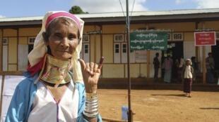 Senhora de minoria étnica mostra a prova de que votou nas eleições legislativas em Myanmar, consideradas as primeiras democráticas em 25 anos.