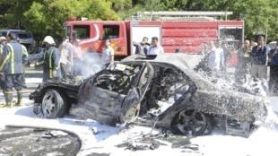 Sírios observam destroços e carro destruído no atentado em Damasco, nesta segunda-feira, dia 28 de abril.