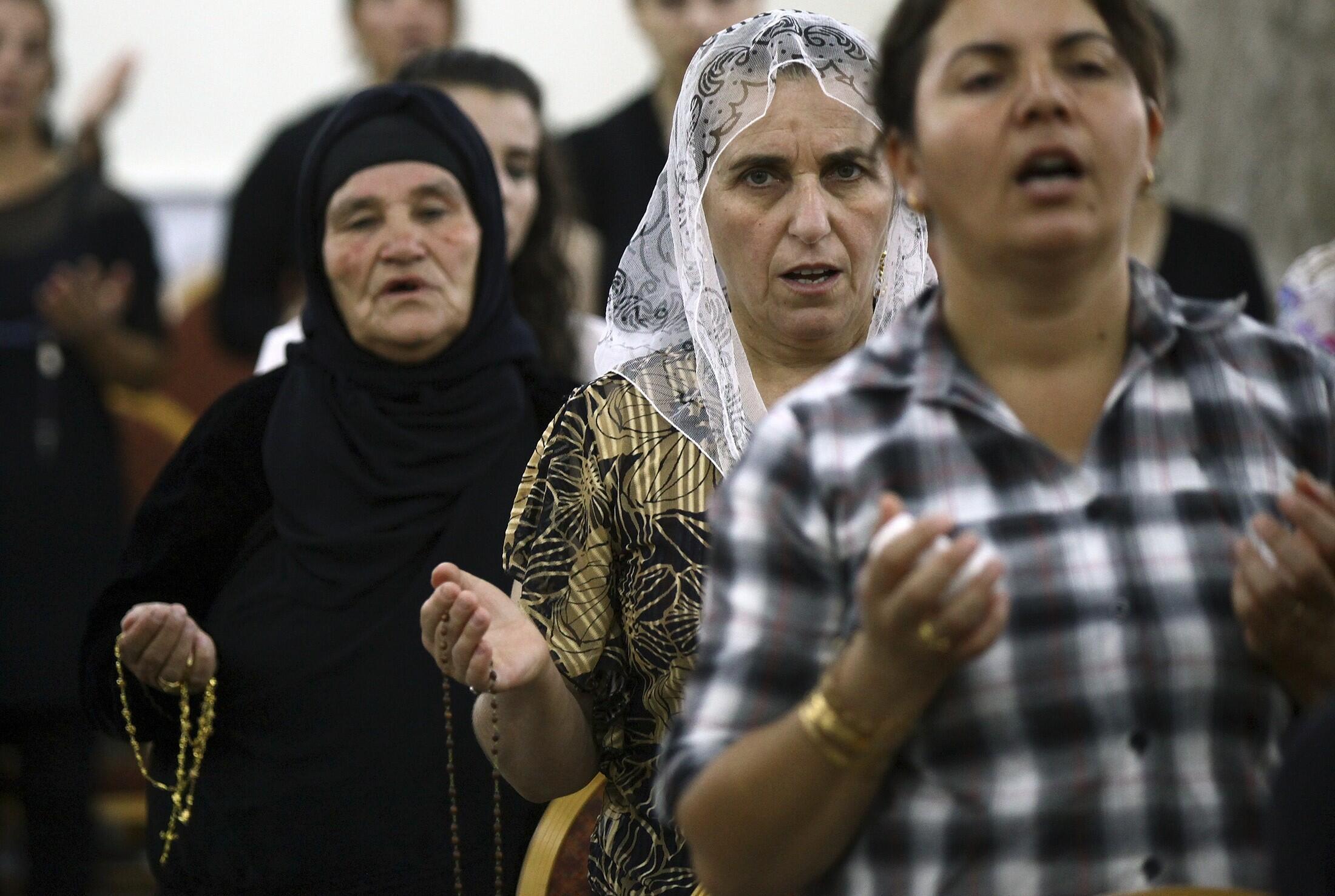 Des chrétiens irakiens qui ont fui les violences à Mossoul, prient dans l'église de Mar Afram à Qaraqush, dans la province de Nineveh, le 19 juillet 2014.