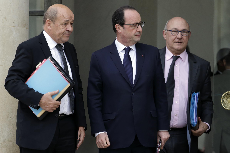 Le président français François Hollande (c), le ministre de la Défense Jean-Yves Le Drian (g) et le ministre des Finances Michel Sapin (d), à la sortie d'un Conseil de Défense à l'Elysée, le 21 janvier 2015.