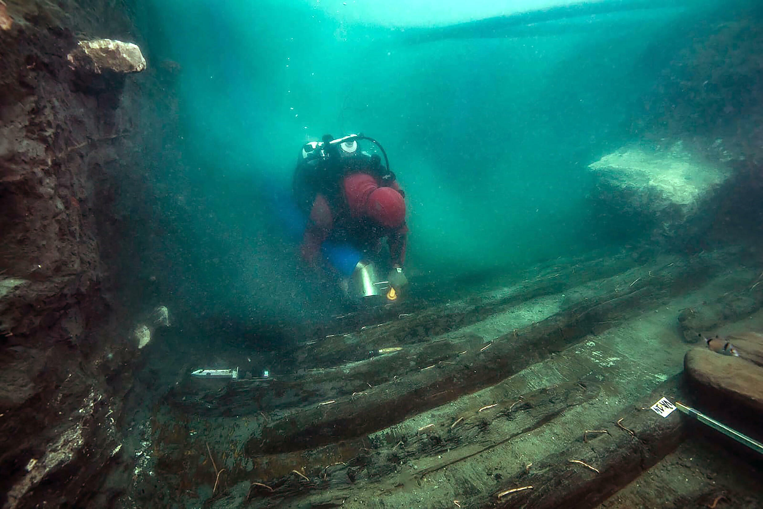 A diver exploring the hull of a military vessel discovered in the sunken city of Thonis-Heracleion on Egypt's Mediterranean coast