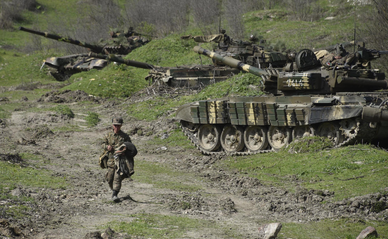 Un soldat de l'armée de défense du Haut-Karabakh passe devant des chars à environ 70 km au nord de Stepanakert, la capitale du Karabakh, le 6 avril 2016.
