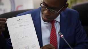 Le ministre haïtien de la Planification et de la Coopération externe Aviol Fleurant montre à la presse la lettre qui retire l'agrément d'ONG à Oxfam GB.