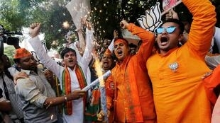 Supporters of Bharatiya Janata Party celebrate after learning of initial poll results in Ahmedabad