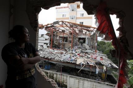 A local resident watches from inside his damaged house as investigators inspect the site of a bombing in the suburbs of Bangkok