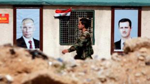 Askari wa Syria akipita karibu na picha za Vladimir Putin na Bashar al-Assad, mashariki mwa Ghouta (Damescus), Februari 28, 2018.