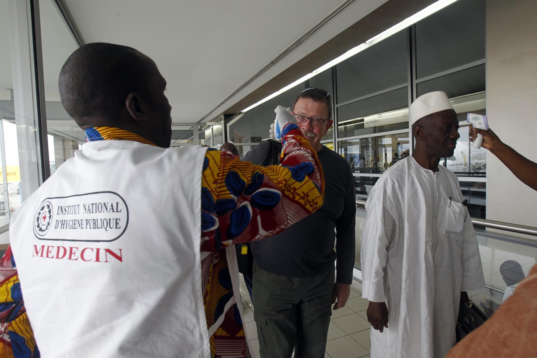 Des passagers se font contrôler à l'aide de thermomètres à infrarouges, dans le cadre de la lutte contre Ebola, à Abidjan, le 13 juin 2014.