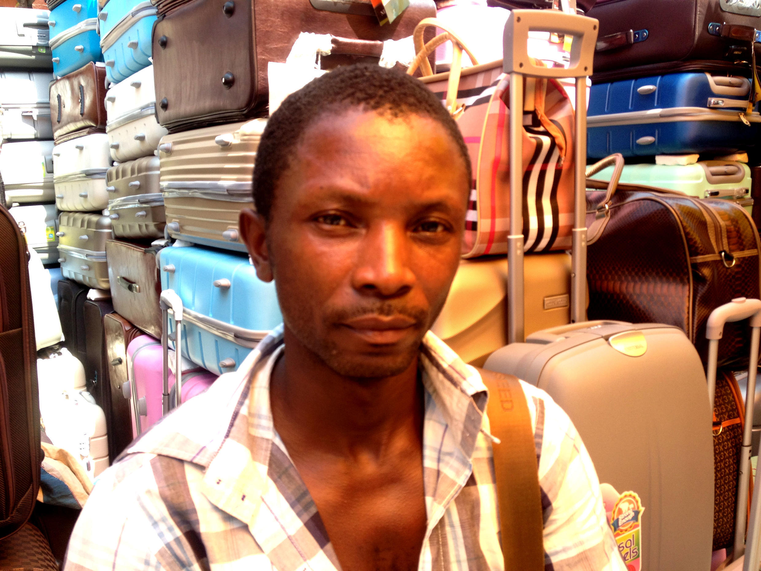Vendor Christian Kyei is having a hard time selling enough suitcases to make a living.