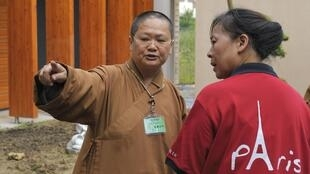 Venerable Manchien Shih who is in charge of the European Regional Temple, directs a worker at the temple in Bussy-Saint Georges