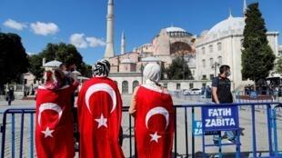 Des personnes portant des drapeaux turcs devant l'ex-basilique Sainte-Sophie, après une décision de justice qui ouvre la voie à sa reconversion de musée en mosquée, à Istanbul, le 10 juillet 2020.