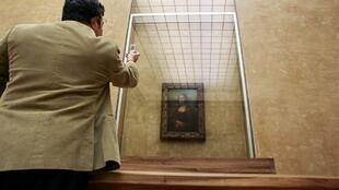 A visitor to the Louvre snaps Leonardo da Vinci's Mona Lisa