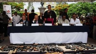 L'aumônier militaire Fabio Colindres aux côtés de Jose Miguel Insulza prend la parole devant un parterre d'armes déposées par les maras.