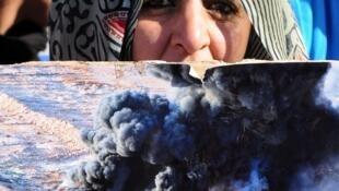 Une femme brandit une image des événements du 8 novembre 2010 près du camp de Gdim Izik, à Rabat le 8 février 2013.