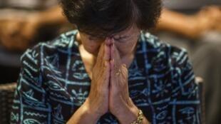 Một phụ nữ cầu nguyện cho các gia đình nạn nhân chuyến bay MH17 tại phi trường Kuala Lumpur
