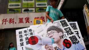 El estudiante activista Joshua Wong porta una pancarta de Nathan Law, candidato del partido Demosisto durante las elecciones para el Consejo Legislativo en Hong Kong, China, septiembre 4, 2016.