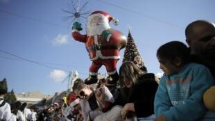 Fiéis celebram o Natal em frente à Basílica da Natividade, em Belém.