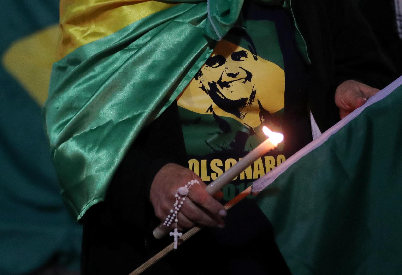 Mulher acende vela para o candidato à Presidência, Jair Bolsonaro, após ele ser esfaqueado durante ato público em Juiz de Fora, 6 de setembro 2018