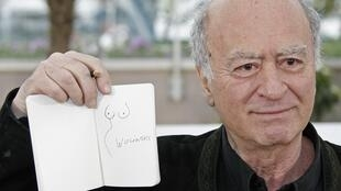 French cartoonist, Georges Wolinski, displays one of his drawings during a photocall at the 61st Cannes Film Festival in 2008.