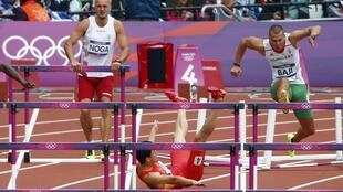 刘翔在预选赛中试图跨越第一个栏时摔倒在地