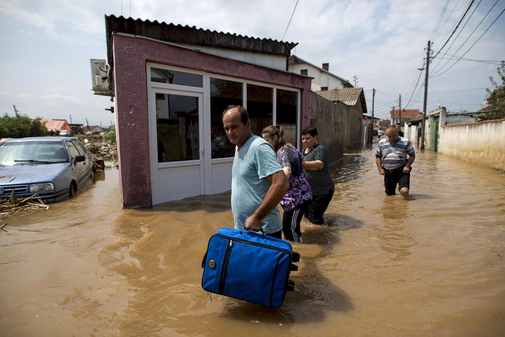 Des habitants de Stakkovci, près de Skopje, en Macédoine, photographiés alors qu'ils s'échappent des inondations dues à de violents orages, le 7 août 2016.