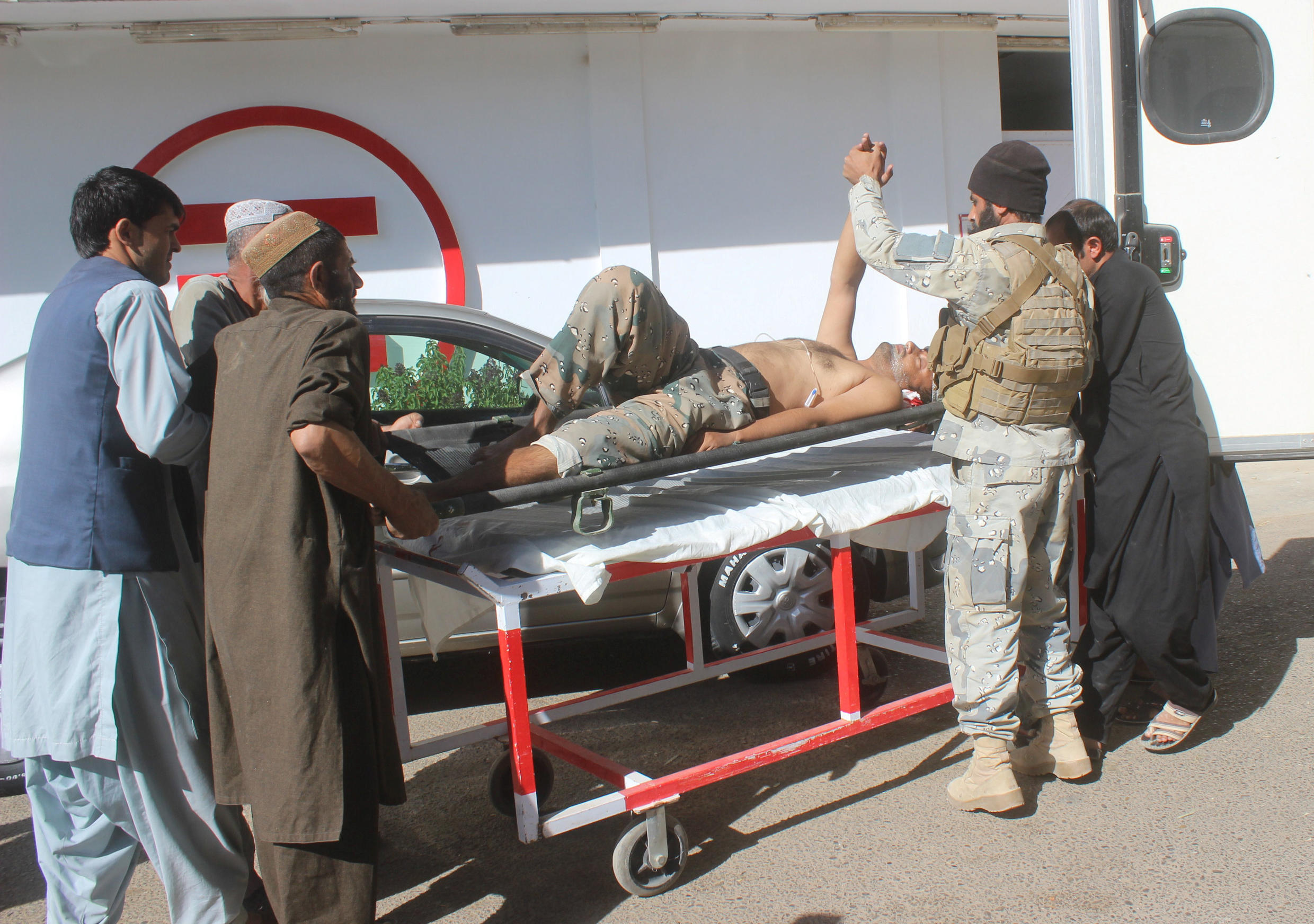 Afghan security forces members carry an injured policeman to a hospital after a blast in Helmand, Afghanistan October 17, 2018.
