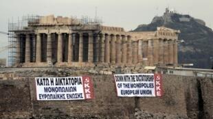 """Al pie de la Acrópolis en Atenas, banderolas incitan a acabar con la """"dictadura""""  de la Unión Europea,  11 de febrero de 2012."""