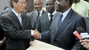 Le président de la Commission électorale ivoirienne, Begre Mambe (D), remet la liste des candidats à l'envoyé spécial des Nations unies, Y J. Choi.