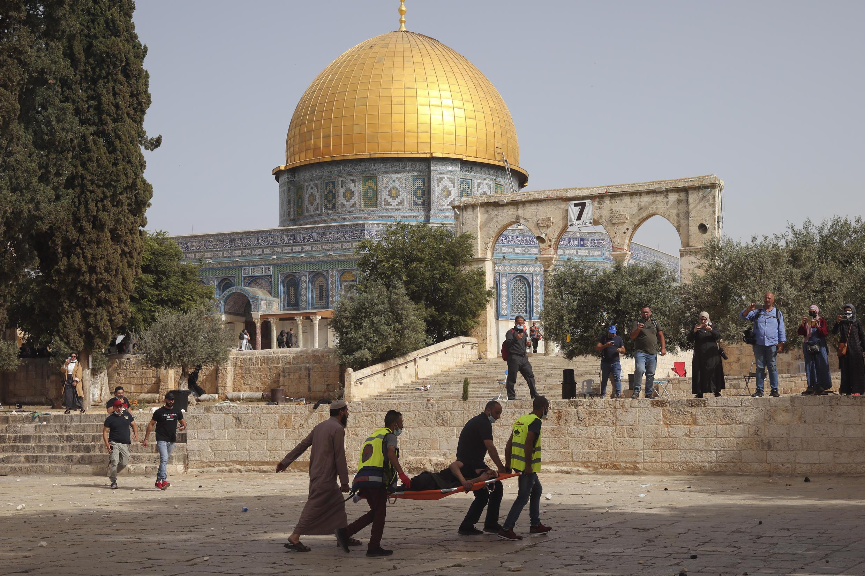 Palestinos evacuan a un hombre herido durante los enfrentamientos con las fuerzas de seguridad israelíes frente a la Cúpula de la Roca en el complejo de la mezquita de Al Aqsa en la Ciudad Vieja de Jerusalén el lunes 10 de mayo de 2021.