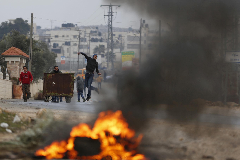 Manifestante joga pedra durante confronto com tropas israelenses em protesto contra assentamento na Cisjordânia.