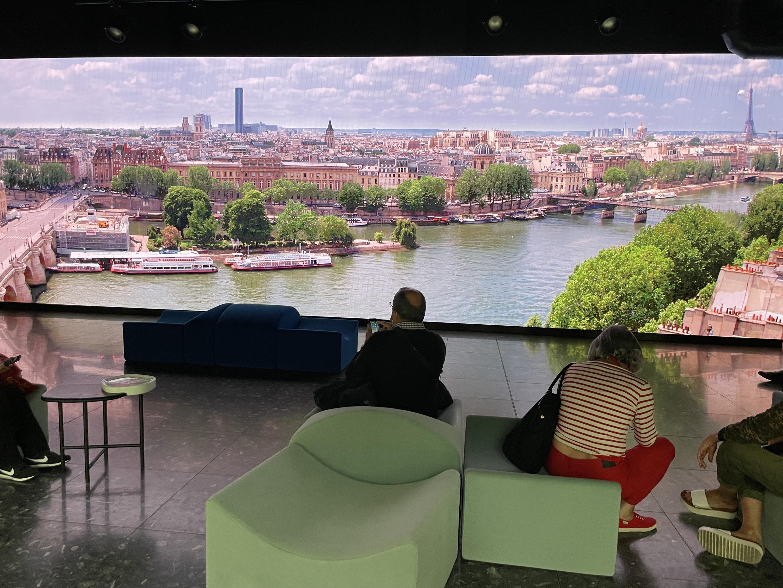 Local de descanso dentro de La Samaritaine, donde una gran pantalla muestra escenas a orillas del río Sena.