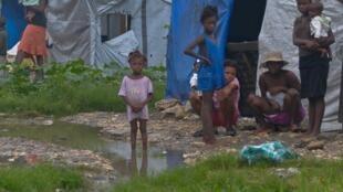 Criança em contato com água suja e contaminada, em acampamento de famílias desabrigadas por causa do furacão Sandy, na cidade de Porto Príncipe, no Haiti.