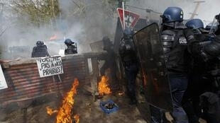 Gendarmes pass a burning shack at Notre-Dame-des-Landes on Monday