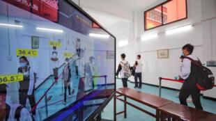 Estudiantes de secundaria pasan por un escáner que toma la temperatura corporal de los alumnos en una escuela en Wuhan, en la provincia central china de Hubei, el 6 de mayo de 2020