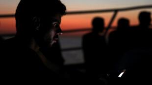 Un migrant cherche à joindre sa famille à bord du navire de l'ONG espagnole « Proactiva Open Arms » alors qu'ils rejoignent le port de Trapani en Sicile.