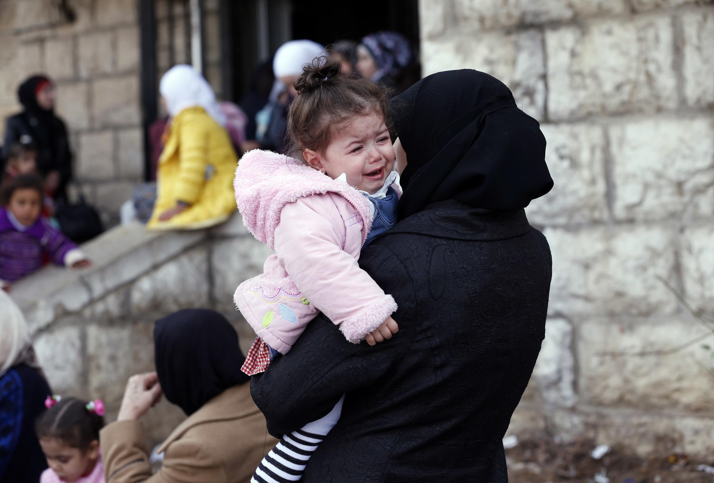 Uma mulher palestina e sua filha no campo de refugiados de Yarmouk, na capital da Síria.