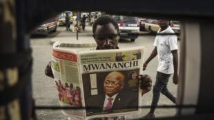 Un hombre lee un periódico con la noticia en primera página de la muerte del presidente tanzano, John Magufuli, el 18 de marzo de 2021 en Dar es Salam