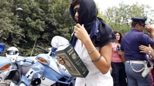 Une jeune femme, qui fait partie d'un groupe d'hôtesses recrutées par une agence romaine, se rend au centre culturel libyen à Rome pour une rencontre avec le leader libyen Mouammar Kadhafi, le 30 août 2010.