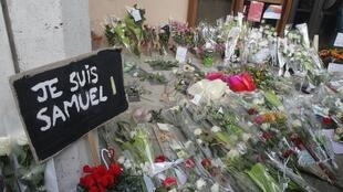 Floral tributes were left outside the college where Samuel Paty taught.