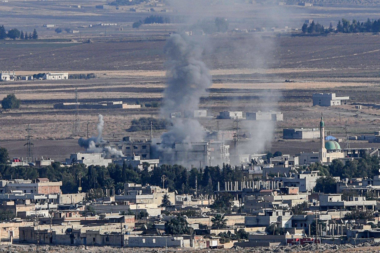 Photo prise du côté turc où l'on aperçoit de la fumée dans la ville syrienne de Ras al-Aïn qui se trouve en face de la ville turque de Ceylanpınar, de l'autre côté de la frontière.