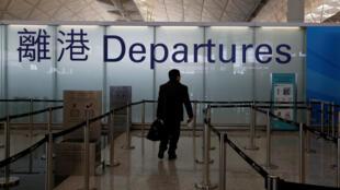 存檔圖片:香港國際機場 出關 Image d'archive: A passenger walks into the departure immigration counter at Hong Kong International Airport in Hong Kong, China