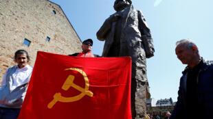 មនុស្សគាំទ្រទ្រឹស្តីរបស់ Karl Marx ឈរថតក្បែររូបសំណាកដែលជាអំណោយរបស់ចិន នៅក្រុង Trier។ ថ្ងៃទី៥ ឧសភា ២០១៨