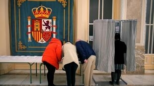 Des électeurs se préparent glisser leurs bulletins, dans un bureau de vote de Madrid, le 28 avril 2019.
