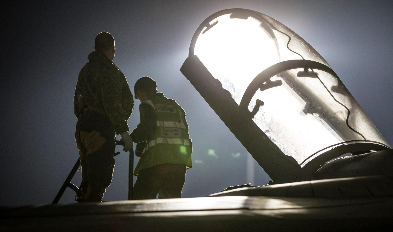 A British Tornado Navigator pilot getting into the cockpit, in Akrotiri, Cyprus, before an air strike on Syria