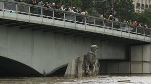 Turistas e curiosos fotografam a estátua Zouave, na Ponte de l'Alma, que virou símbolo das enchentes em Paris.