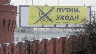 Membros do movimento de oposição Solidariedade conseguiram pendurar uma faixa contra a candidatura de Vladimir Putin num prédio em frente ao Kremlim, em Moscou.